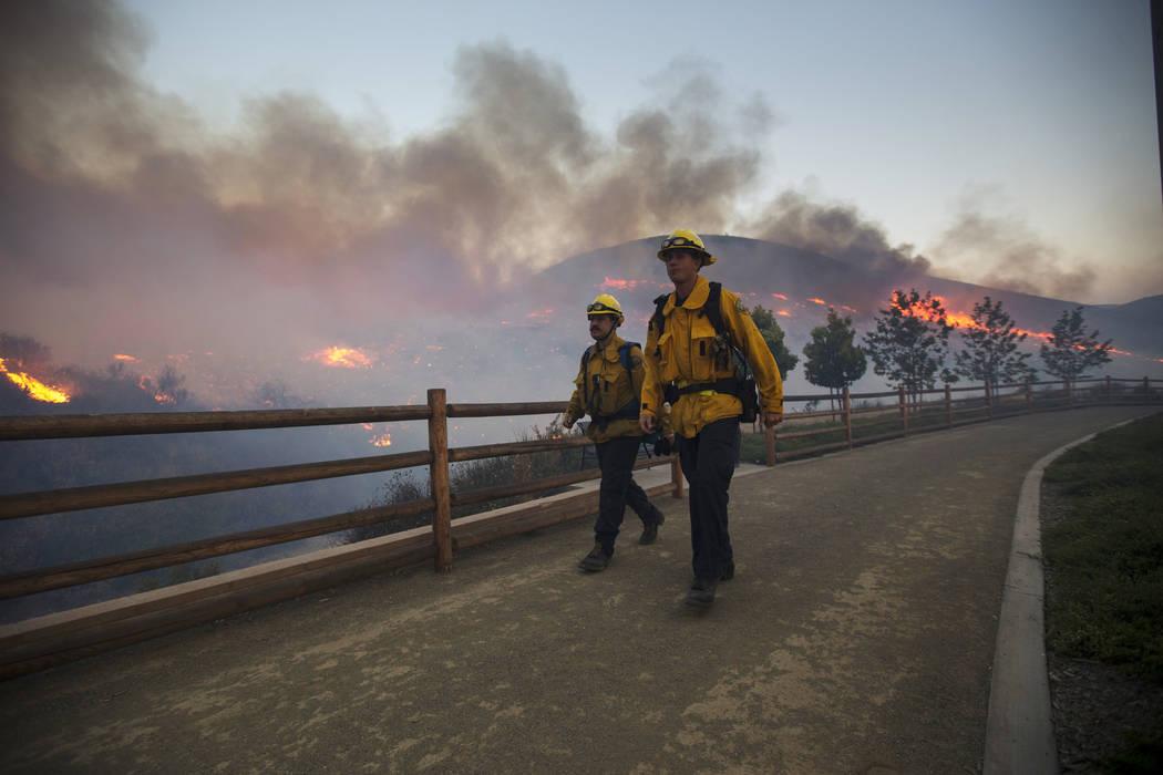 Firefighters walk by a wildfire burning on a hillside near the Westlake Village Community Park in Westlake Village, Calif., on Friday, Nov. 9, 2018. Richard Brian Las Vegas Review-Journal @vegasph ...