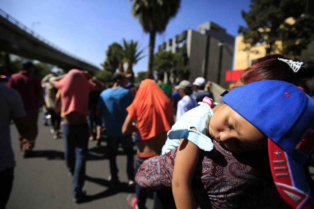 A sleeping Honduran girl is carried as a group of Central American migrants, representing the thousands participating in a caravan trying to reach the U.S. border, undertake an hours-long march to ...