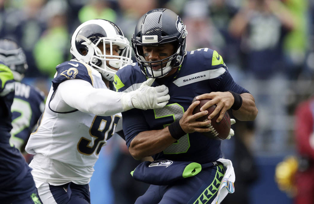 Seattle Seahawks quarterback Russell Wilson, right, is sacked by Los Angeles Rams defensive tackle Aaron Donald, left, during the first half of an NFL football game, Sunday, Oct. 7, 2018, in Seatt ...
