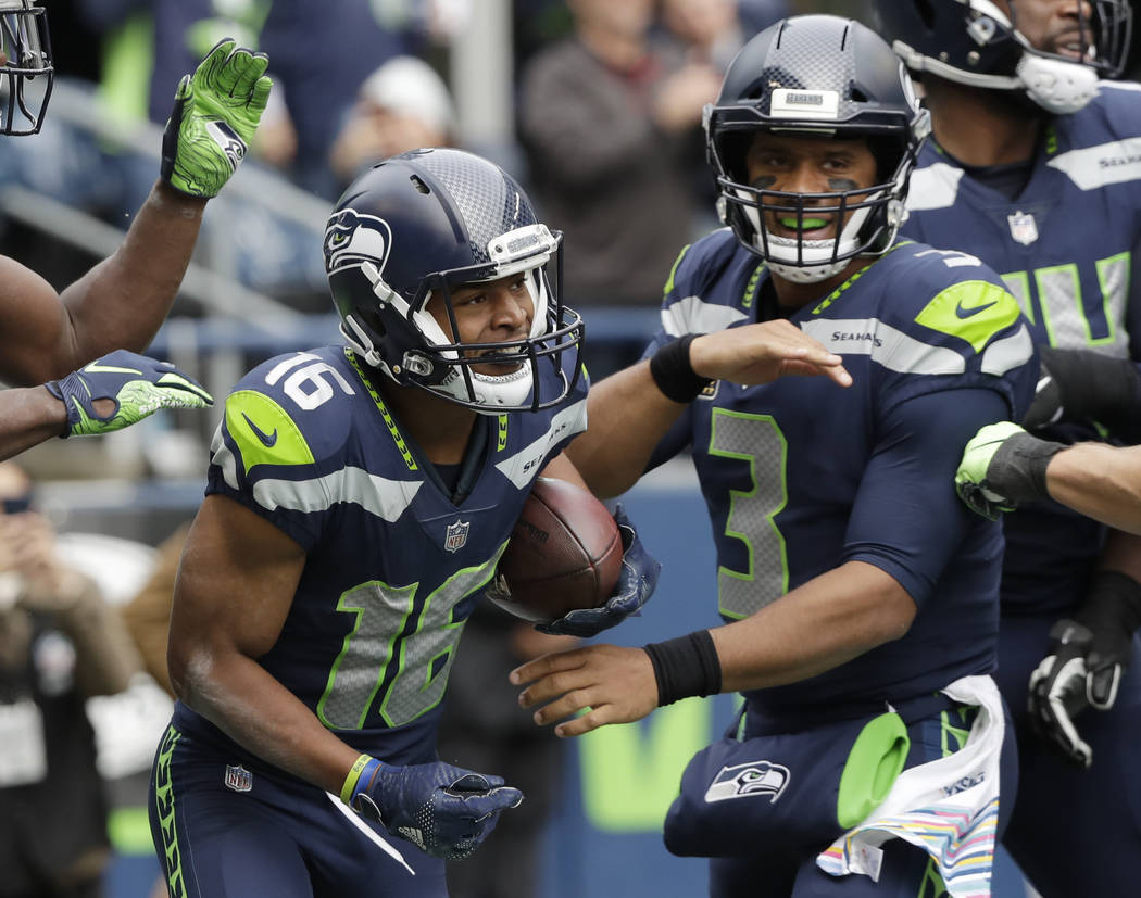 Seattle Seahawks wide receiver Tyler Lockett, left, is greeted by quarterback Russell Wilson after Lockett made a catch for a touchdown against the Los Angeles Rams during the first half of an NFL ...