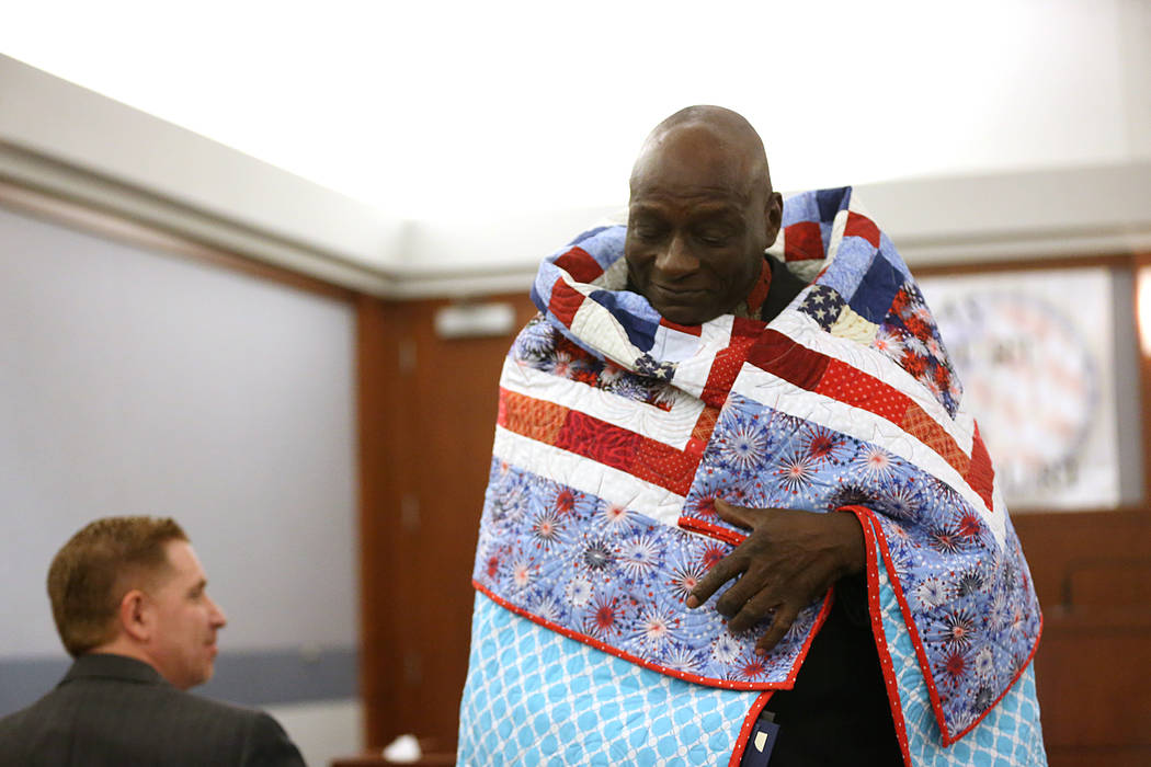 Veterans' court graduate Navy Veteran Edward Smith is wrapped with a quilt presented to him by Quilts of Valor during the Veterans Treatment Court Promotion and Graduation Day at the Regional Just ...