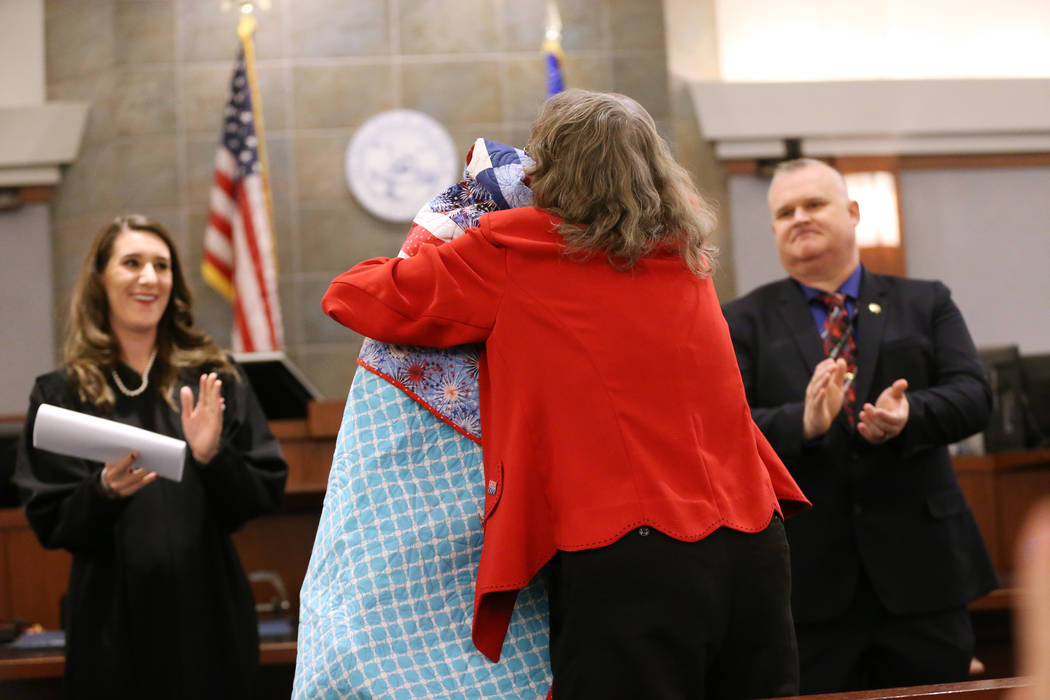Quilts of Valor's Jarenie Trachier, right, hugs veterans' court graduate Navy Veteran Edward Smith after presenting him with a quilt during the Veterans Treatment Court Promotion and Graduation Da ...