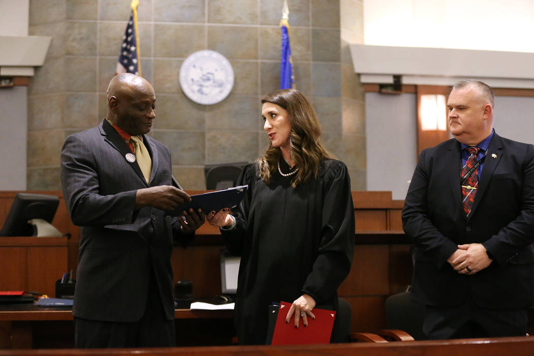 Navy Veteran Edward Smith, from left, with Judge Harmony Leticia and Las Vegas Metropolitan Police Department Deputy Chief Richard Forbus, during the Veterans Treatment Court Promotion and Graduat ...