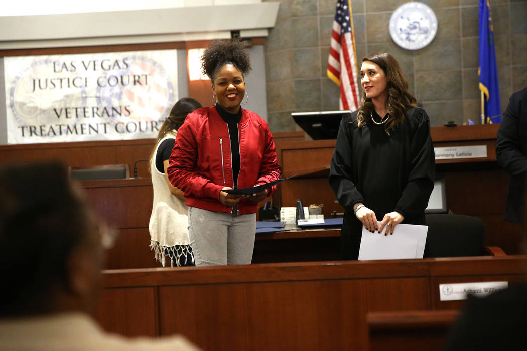 Army veteran Brittany Payne-Purse, left, with Judge Harmony Leticia, is recognized for her promotion during the Veterans Treatment Court Promotion and Graduation Day at the Regional Justice Center ...