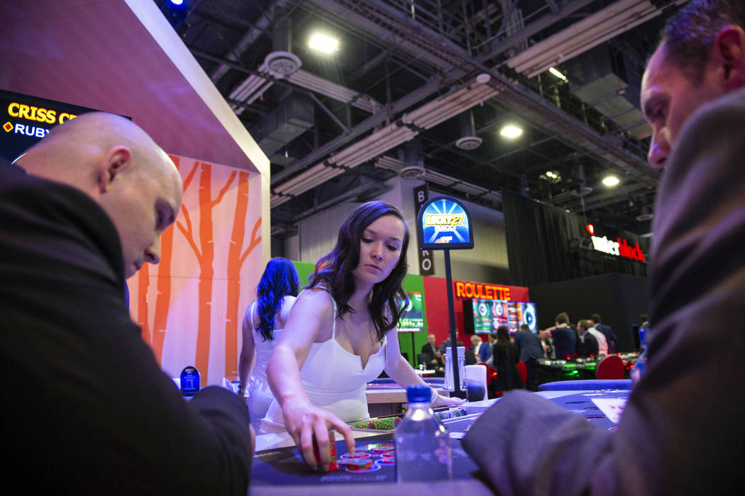 Olivia Paiz of Las Vegas deals poker chips at the AGS Criss Cross Poker table at the 18th annual Global Gaming Expo at Sands Expo and Convention Center in Las Vegas, Wednesday, Oct. 10, 2018. Caro ...