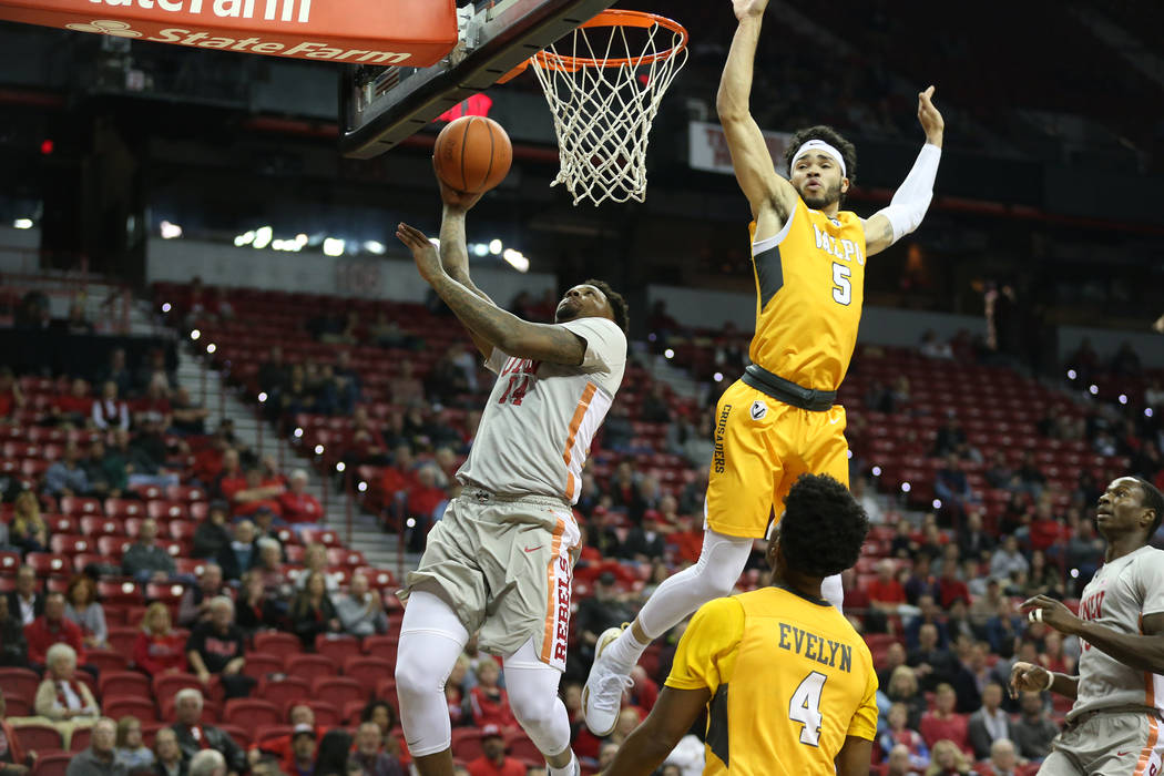 UNLV Rebels forward Tervell Beck (14) takes a shot against pressure from Valparaiso Crusaders guard Markus Golder (5) during the first half of the basketball game at the Thomas & Mack Center i ...