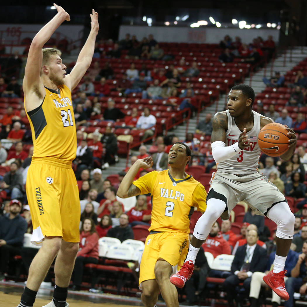 UNLV Rebels guard Amauri Hardy (3) makes a pass under pressure from Valparaiso Crusaders center Derrik Smits (21) and guard Deion Lavender (2) during the second half of the basketball game at the ...