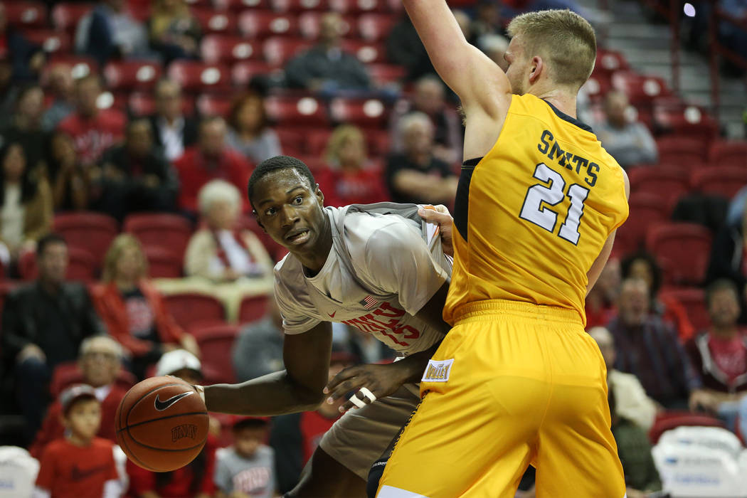 UNLV Rebels forward Cheickna Dembele (15) looks for an open pass under pressure from Valparaiso Crusaders center Derrik Smits (21) during the first half of the basketball game at the Thomas & ...