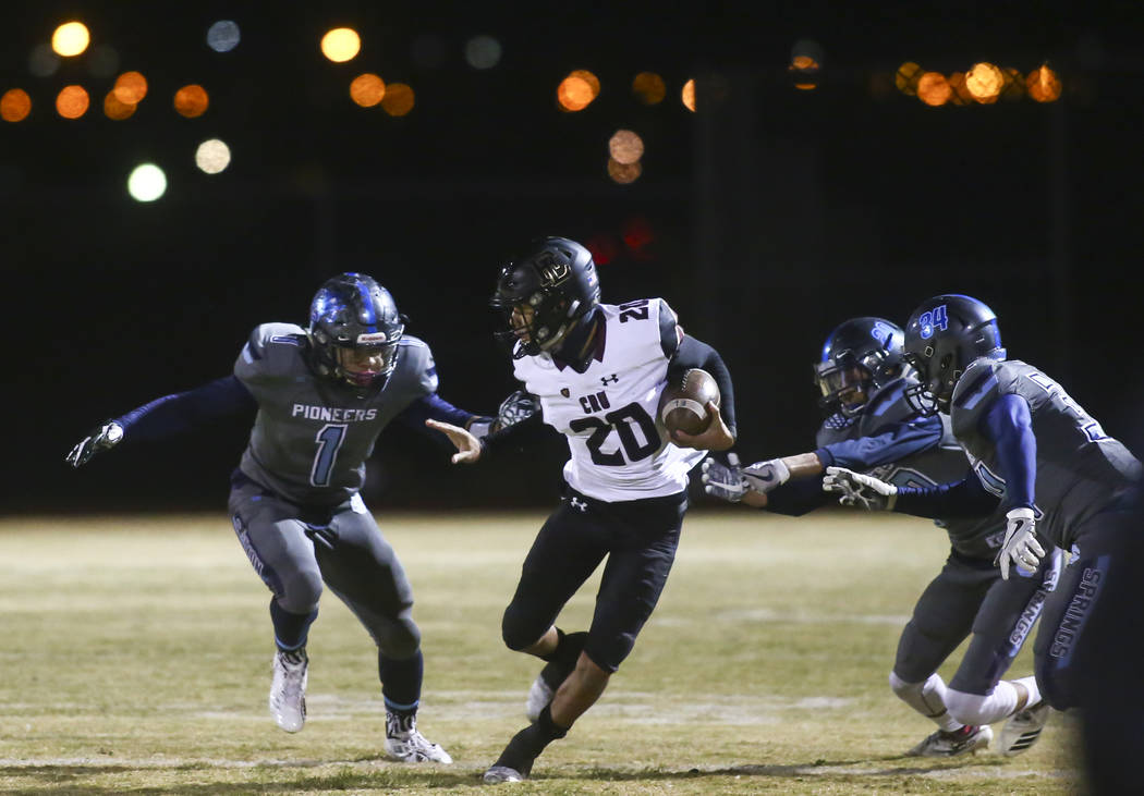 Faith Lutheran's Gregory Oliver (20) runs past Canyon Springs' Gianni Blackwell (1) during a Mountain Region football semifinal game at Canyon Springs High School in North Las Vegas on Friday, Nov ...