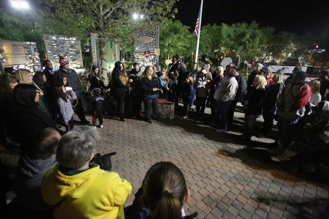 A crowd, that includes survivors from the Las Vegas mass shooting, gathers for a vigil at the Las Vegas Healing Garden on Friday, November 9, 2018, to honor the 12 people killed in the Borderline ...