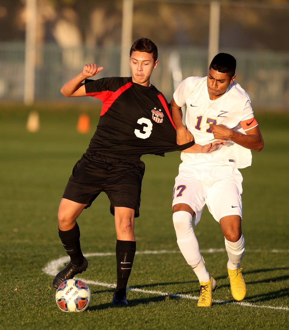 Las Vegas' Carlos Sanchez (3) and Durango's Marcos Delgado (17) battle for the ball in the first half of their Class 4A state boys soccer semifinal game at Bettye Wilson Soccer Complex in Las Vega ...
