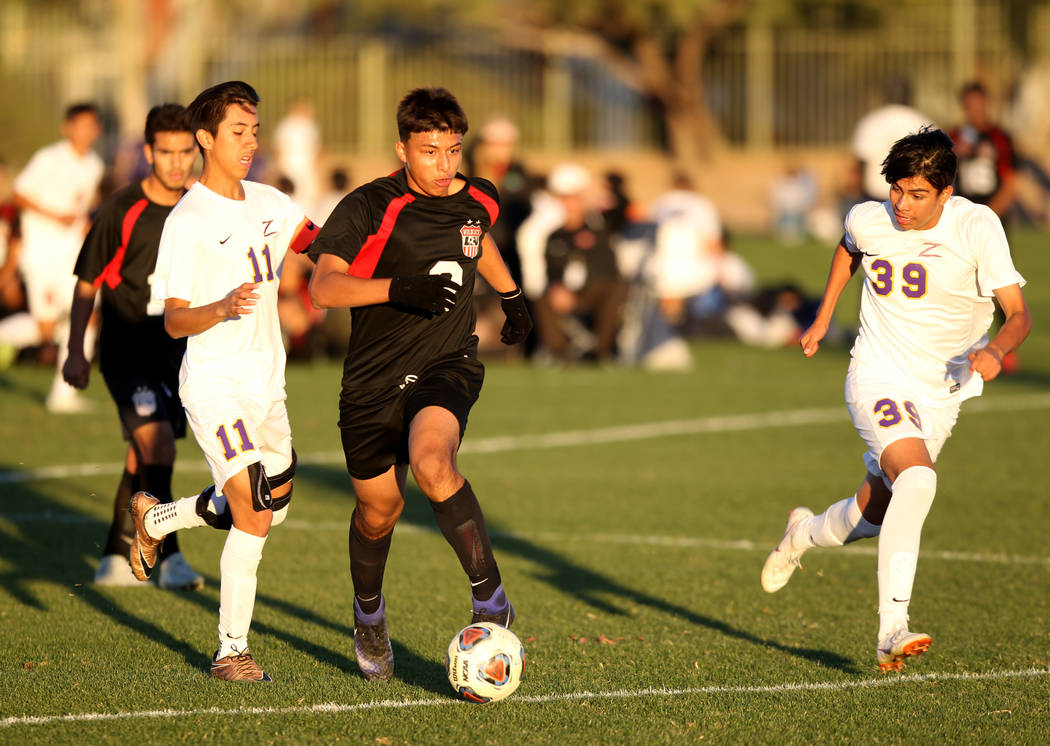 Las Vegas' Daniel Rangel (8) moves the ball between Durango's Christopher Bramasco (11) and Durango's Adonis Rodriguez (39) in the first half of their Class 4A state boys soccer semifinal game at ...