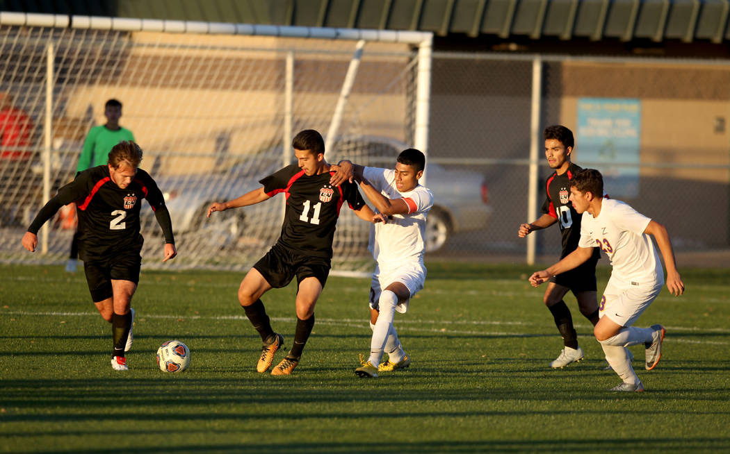 Las Vegas' Drew Bowden (2) and Rigo Carrasco (11) move the ball in front of Durango's Marcos Delgado (17) in the first half of their Class 4A state boys soccer semifinal game at Bettye Wilson Socc ...