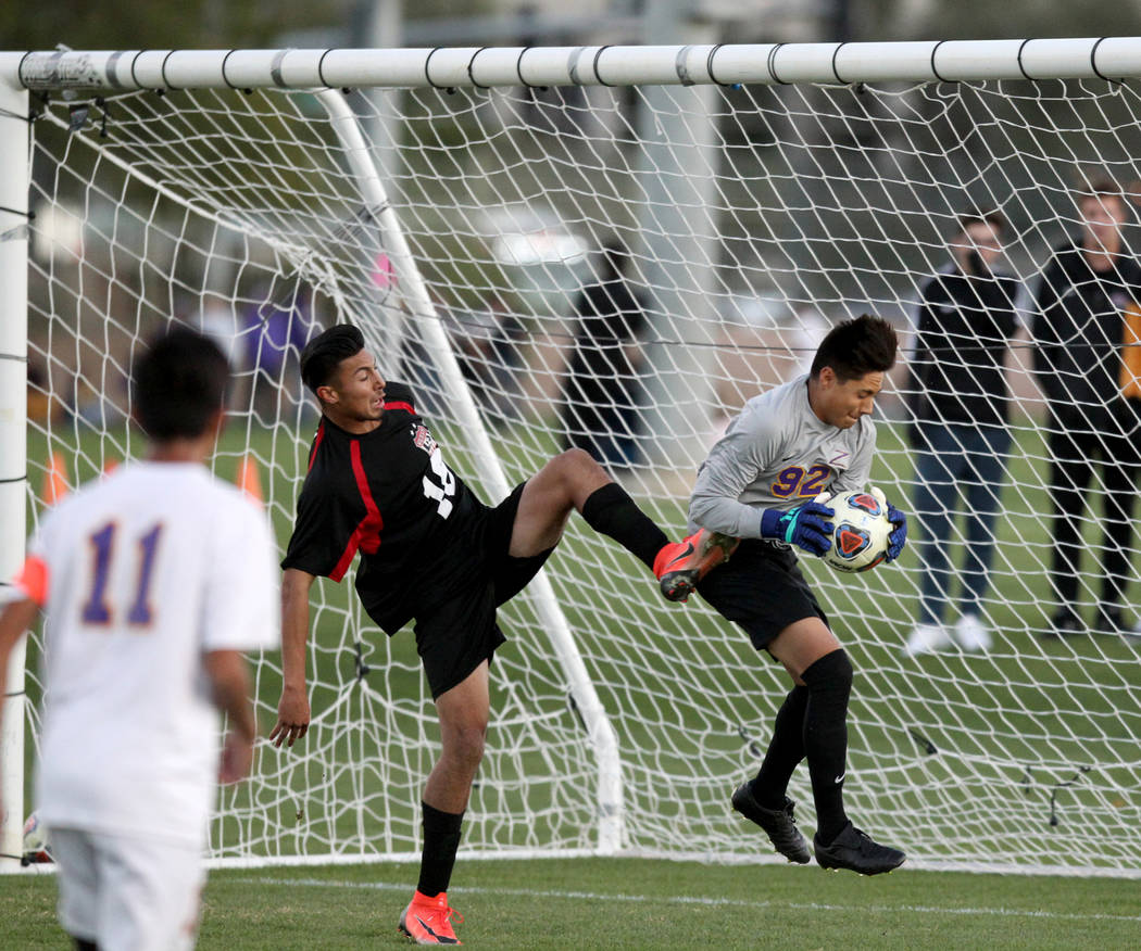 Durango's Jason Sotelo (92) makes a save in front of Las Vegas' Nathan Zamora (16) in the first half of their Class 4A state boys soccer semifinal game at Bettye Wilson Soccer Complex in Las Vegas ...