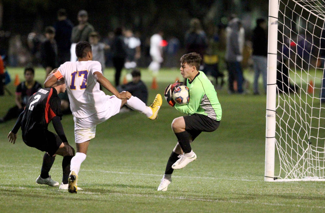 Las Vegas goalie Las Vegas' Rodolfo Gomez (1) saves a shot by Durango's Marcos Delgado (17) as Las Vegas' Drew Bowden (2) looks on in the second half of their Class 4A state boys soccer semifinal ...