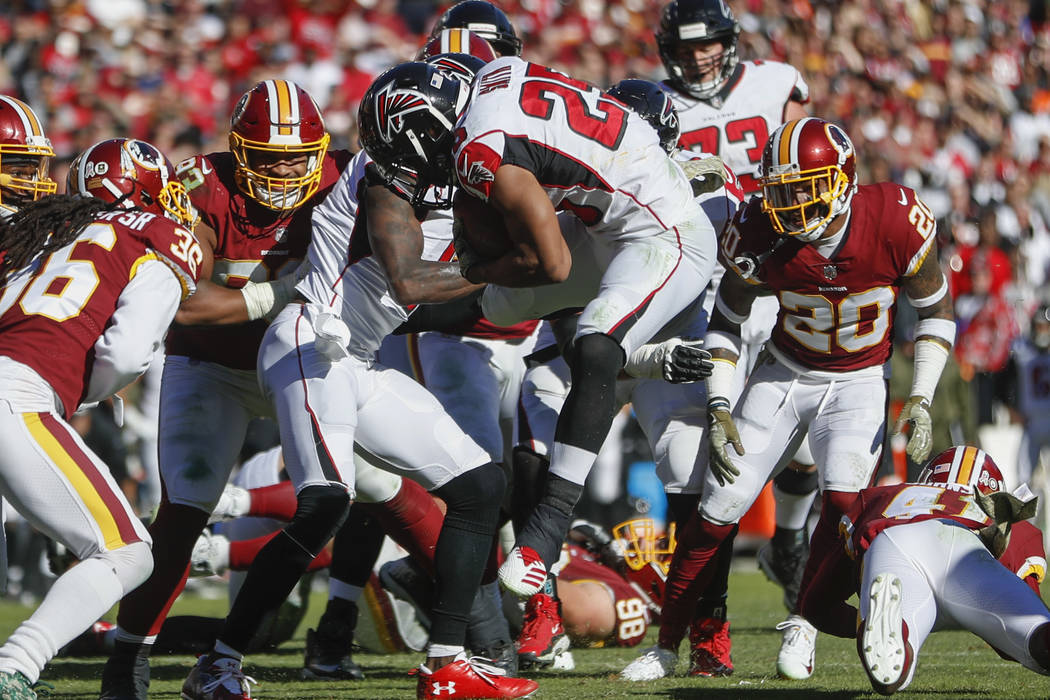 Atlanta Falcons running back Ito Smith (25) leaps toward the end zone for a touchdown during the first half of an NFL football game against the Washington Redskins, Sunday, Nov. 4, 2018, in Landov ...