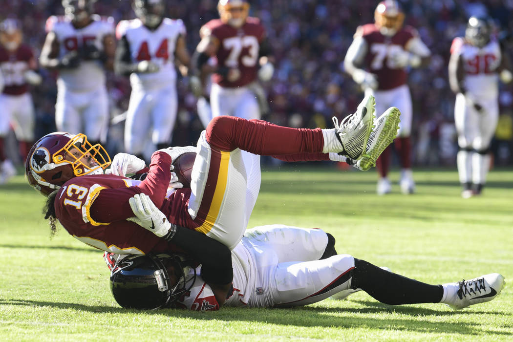 Washington Redskins wide receiver Maurice Harris (13) is pulled to the turf by Atlanta Falcons cornerback Brian Poole, bottom, during the first half of an NFL football game Sunday, Nov. 4, 2018, i ...