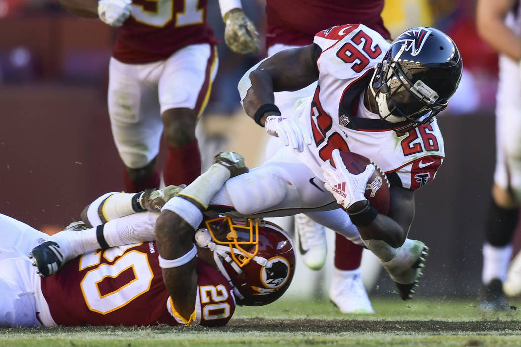 Atlanta Falcons running back Tevin Coleman (26) is stopped by Washington Redskins free safety Ha Ha Clinton-Dix (20) during the second half of an NFL football game Sunday, Nov. 4, 2018, in Landove ...