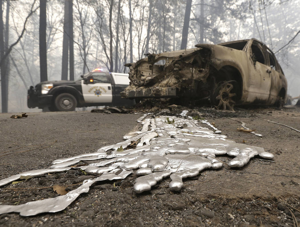 A California Highway Patrol vehicle passes a vehicle Friday, Nov. 9, 2018, destroyed by a wildfire in Paradise, Calif. The wind-whipped fires have destroyed blocks of homes and other property in t ...