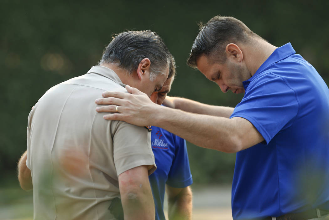 Ventura County Sheriff's Office Capt. Garo Kuredjian, left, embraces chaplains with the Billy Graham Rapid Response Team (RRT) as they pray near the site of Wednesday's mass shooting in Thousand O ...