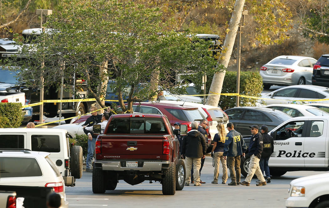 FBI investigators join law enforcement as they work near the scene of Wednesday's shooting in Thousand Oaks, Calif., Friday, Nov. 9, 2018. Investigators continue to work to figure out why an ex-Ma ...
