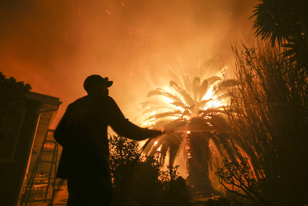 Park Billow, 27, sprays water on the hot spots in his backyard as the Woolsey Fire burns in Malibu, Calif., Friday, Nov. 9, 2018. Authorities announced Friday that a quarter of a million people ar ...
