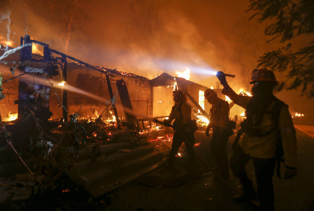 Firefighters battle the Woolsey Fire burning a home in Malibu, Calif., Friday, Nov. 9, 2018. (AP Photo/Ringo H.W. Chiu)