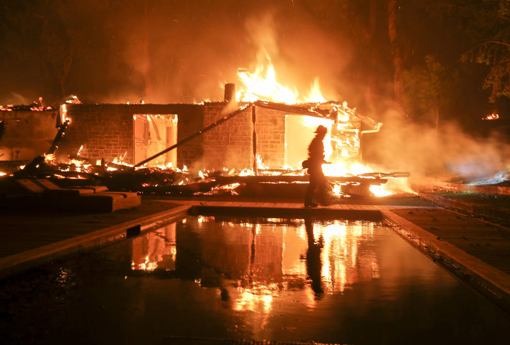 A firefighter walks by the a burning home in Malibu, Calif., Friday, Nov. 9, 2018. A Southern California wildfire continues to burn homes as it runs toward the sea. Winds are blamed for pushing th ...