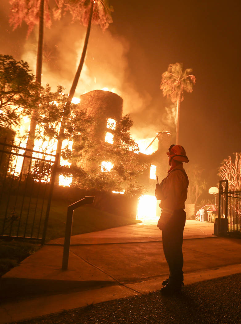 A firefighter keeps watch as the Woolsey Fire burns a home in Malibu, Calif., Friday, Nov. 9, 2018. A Southern California wildfire continues to burn homes as it runs toward the sea. Winds are blam ...