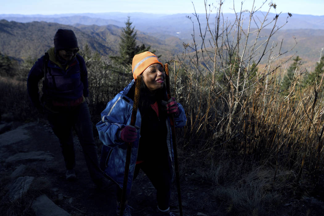 In this Oct. 30, 2018 photo, Tanya Cummings smiles as the sunlight hits her face as she hikes up Waterrock Knob on the Blue Ridge Parkway in Maggie Valley, N.C., with Pathways to Parks. Pathways t ...