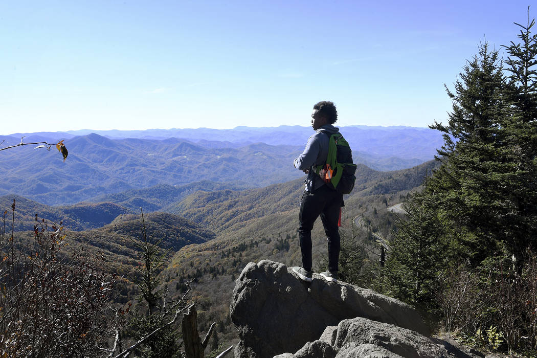 In this Oct. 30, 2018 photo, Joshua Perkins takes in the view from the top of Waterrock Knob on the Blue Ridge Parkway in Maggie Valley, N.C., as he hikes with Pathways to Parks. Pathways to Parks ...