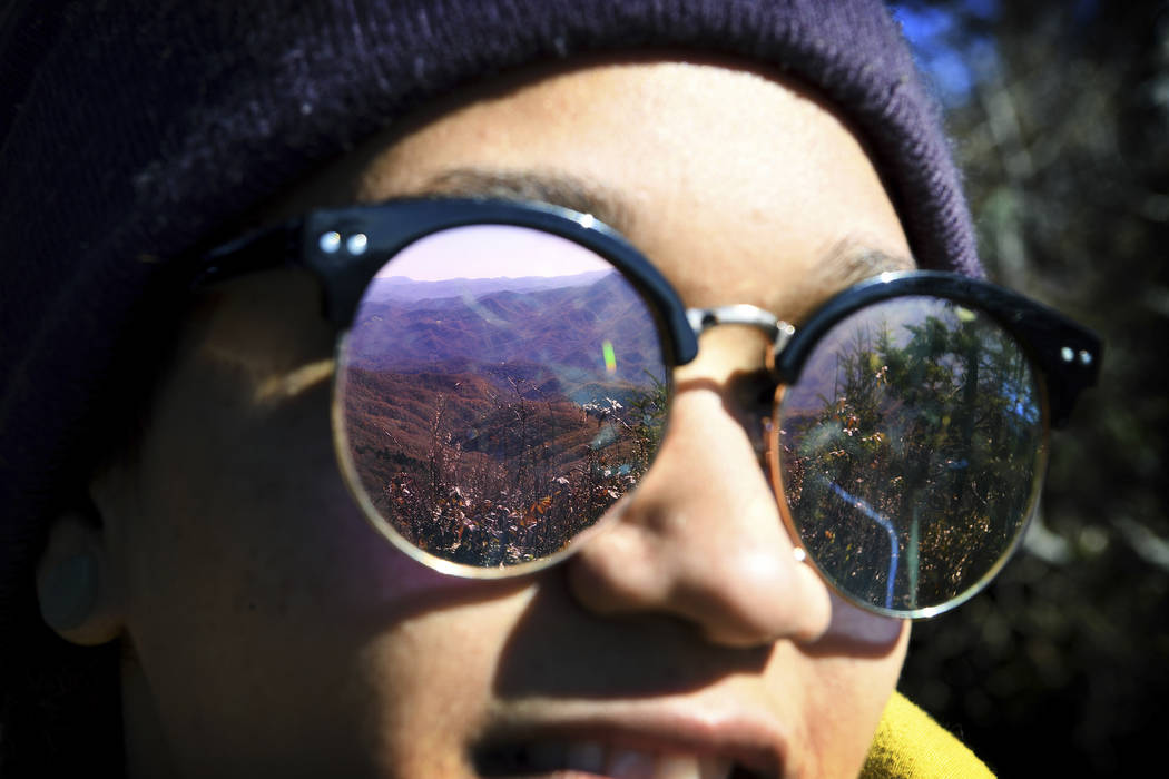 In this Oct. 30, 2018 photo, a mountain view is reflected in Elsea Brown's sunglasses as she hikes Waterrock Knob on the Blue Ridge Parkway in Maggie Valley, N.C., with Pathways to Parks. Pathways ...