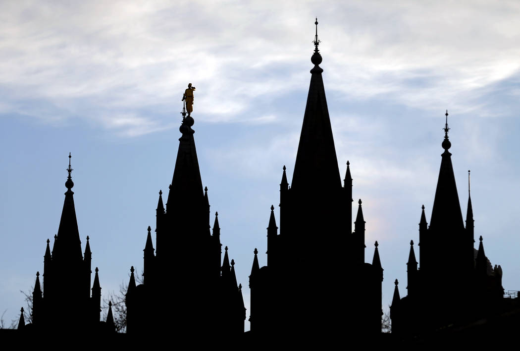FILE- In this Jan. 3, 2018, file photo, the angel Moroni statue, silhouetted against the sky, sits atop the Salt Lake Temple, at Temple Square in Salt Lake City. After months of fierce debate and ...