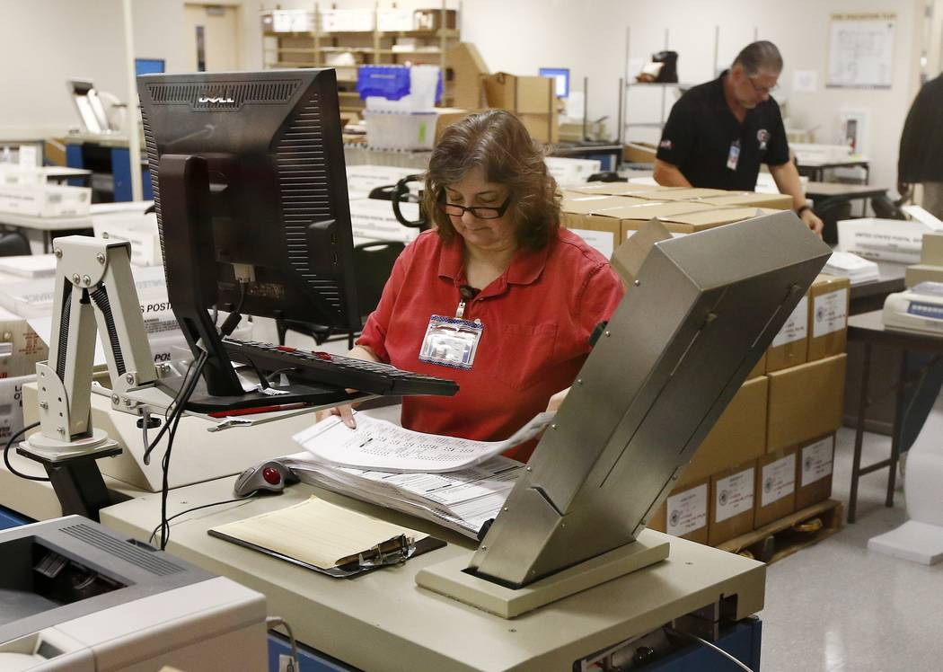 Workers prepare ballots for counting machines at the Maricopa County Recorder's Office Thursday, Nov. 8, 2018, in Phoenix. (AP Photo/Ross D. Franklin)