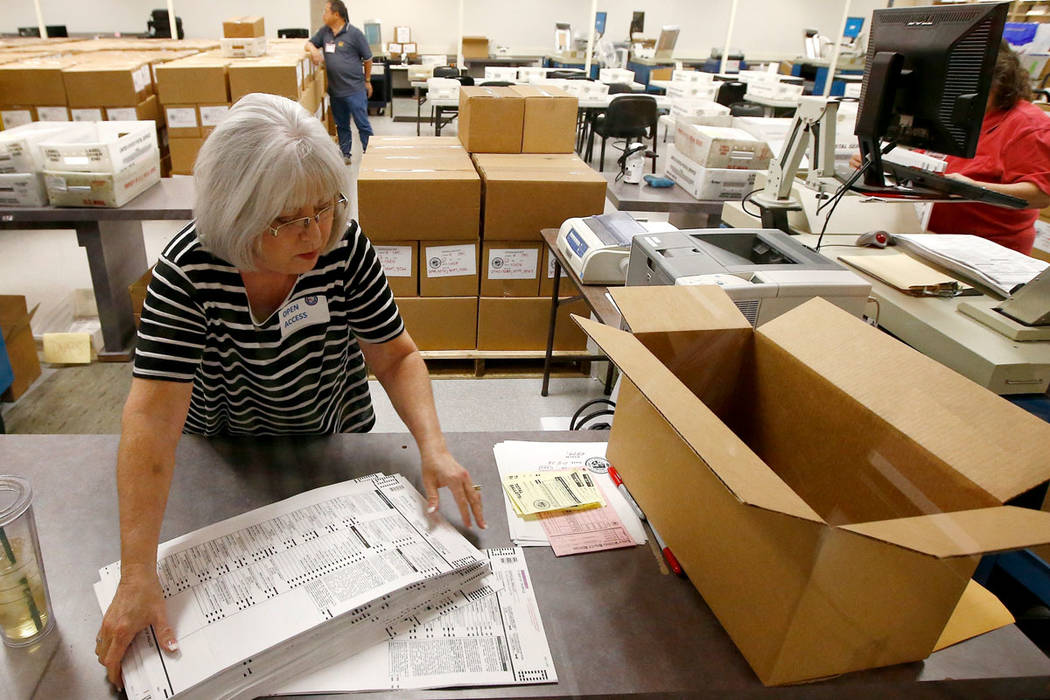 Workers at the Maricopa County Recorder's Office go through ballots Thursday, Nov. 8, 2018, in Phoenix. There are several races too close to call in Arizona, especially the Senate race between Dem ...