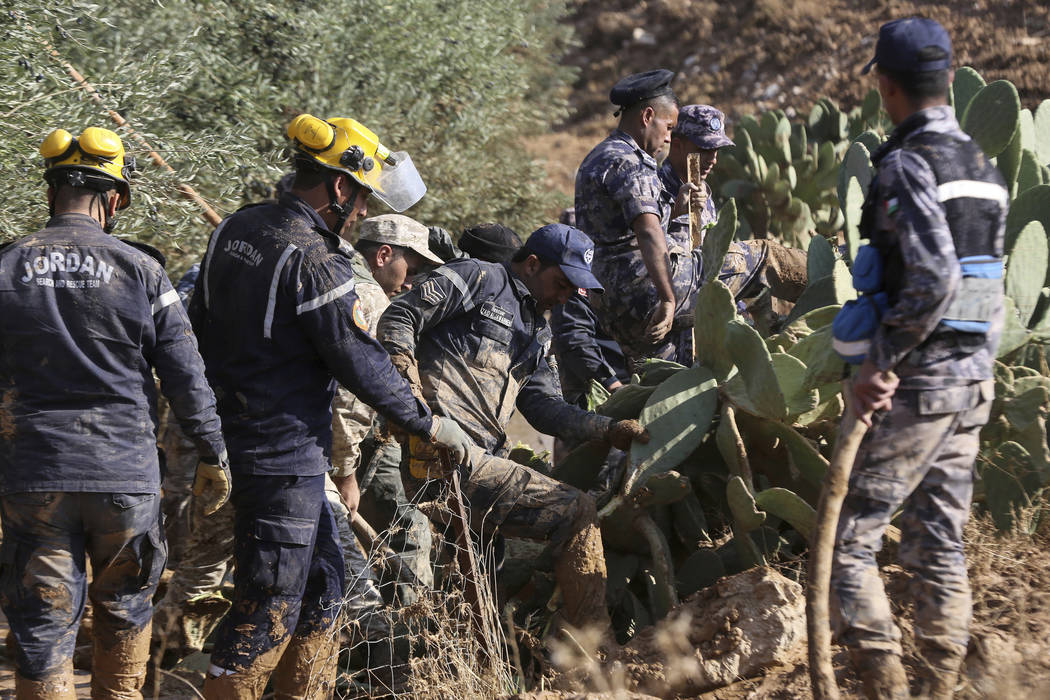 Jordanian rescue teams search Saturday, Nov. 10, 2018 for missing people in the Madaba area, south of the capital of Amman, after flash floods unleashed by heavy rain a day earlier killed several ...