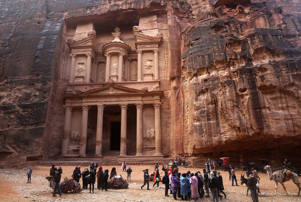 FILE - In this Feb. 13, 2017, file photo, tourists brave a rare rainstorm in plastic ponchos to peer at the Treasury, Jordan's most famous archaeological monument leftover from the Nabatean civili ...