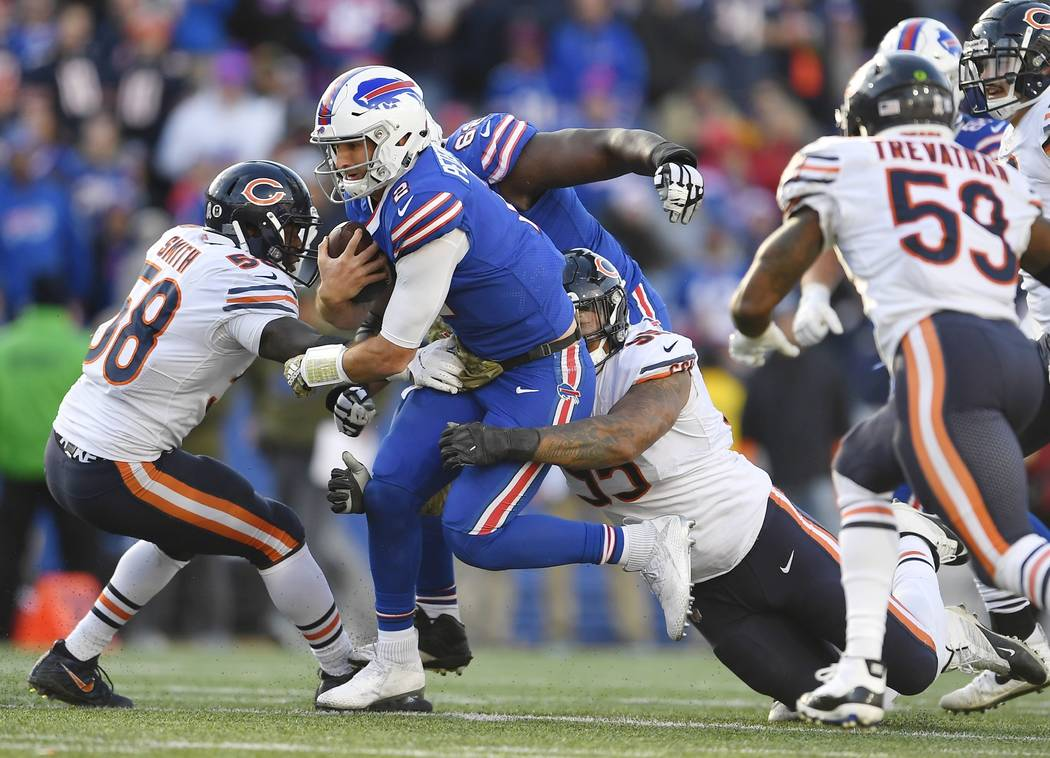 Buffalo Bills quarterback Nathan Peterman (2) is tackled by Chicago Bears' Roy Robertson-Harris (95) and Roquan Smith (58) during the second half of an NFL football game Sunday, Nov. 4, 2018, in O ...