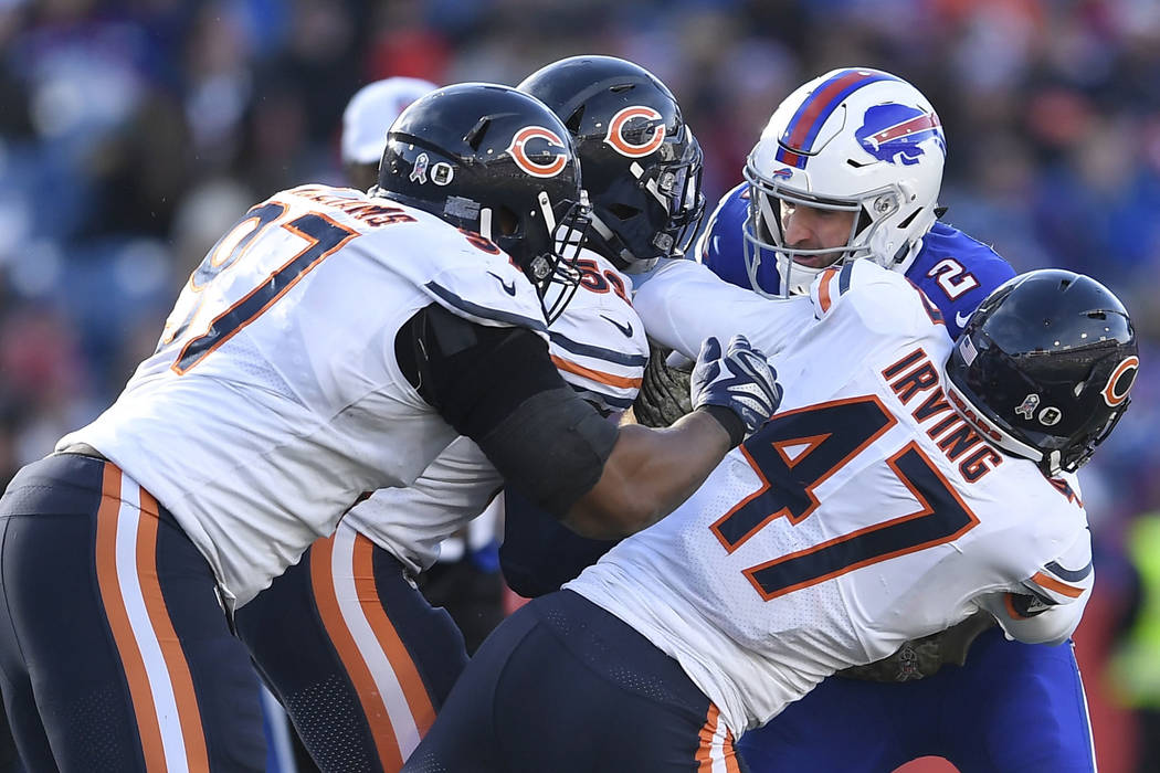 Buffalo Bills' Nathan Peterman (2) is sacked by Chicago Bears' Isaiah Irving (47) and Nick Williams (97) during the second half of an NFL football game Sunday, Nov. 4, 2018, in Orchard Park, N.Y. ...
