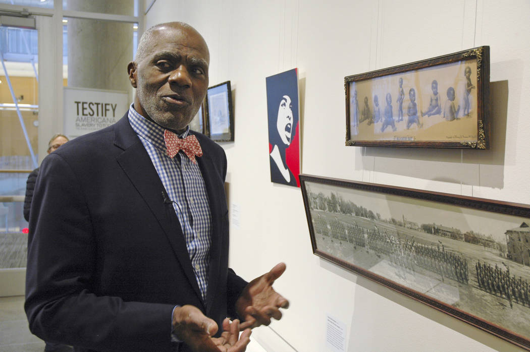 "Alan Page, NFL Hall of Famer and retired Minnesota Supreme Court justice, stands in Minneapolis, by a photo of black babies labeled ""Alligator Bait"" on Jan. 11, 2018. (AP Photo/Steve Karnowski)"