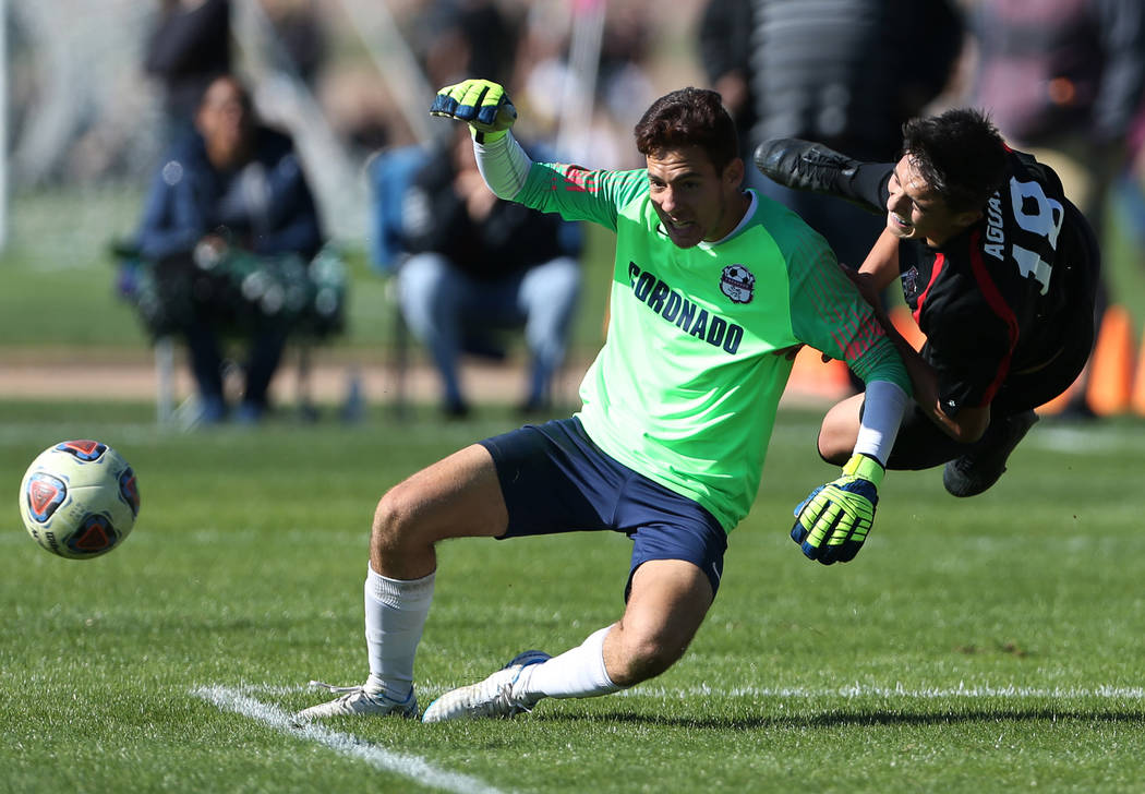 Las Vegas' Sergio Aguayo (18) takes a fall during the second half against Coronado in the 4A boys state soccer championship game at the Bettye Wilson Soccer Complex in Las Vegas, Saturday, Nov. 10 ...