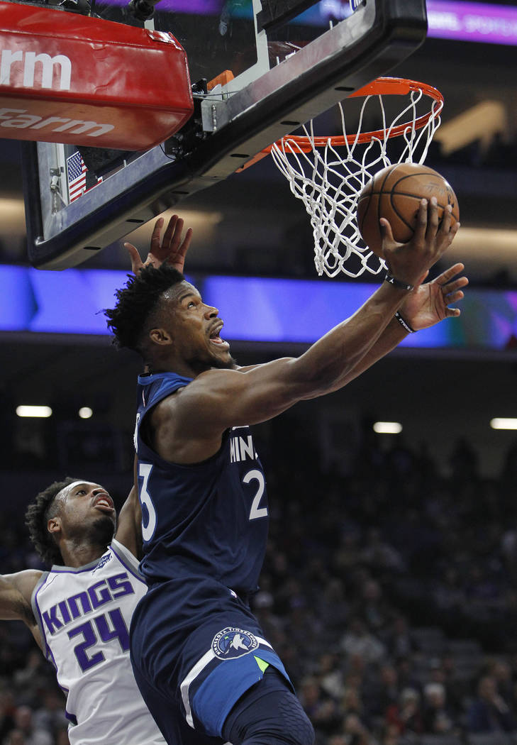 Minnesota Timberwolves guard Jimmy Butler (23) gets around Sacramento Kings guard Buddy Hield (24) for a basket during the first half of an NBA basketball game in Sacramento, Calif., Friday, Nov. ...