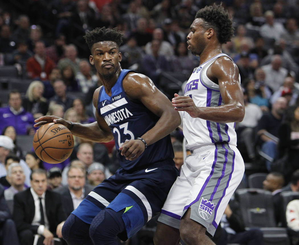Minnesota Timberwolves guard Jimmy Butler (23) battles for position against Sacramento Kings guard Buddy Hield (24) during the first half of an NBA basketball game in Sacramento, Calif., Friday, N ...