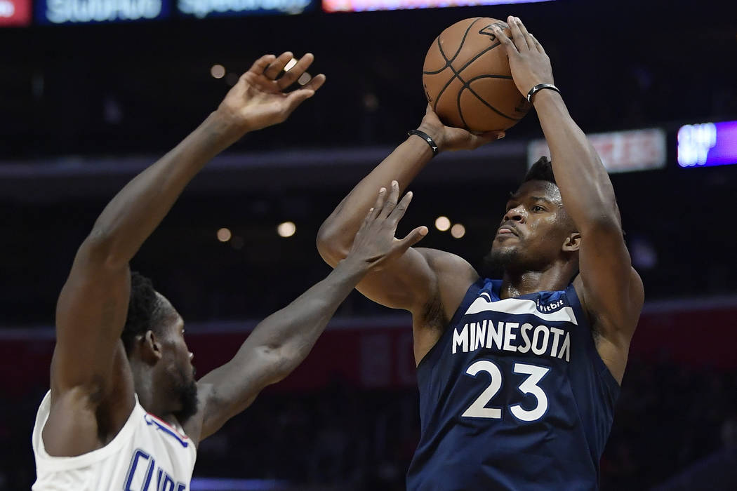 This Nv. 5, 2018, file photo shows Minnesota Timberwolves guard Jimmy Butler, right, shooting as Los Angeles Clippers guard Patrick Beverley defends during the second half of an NBA basketball gam ...
