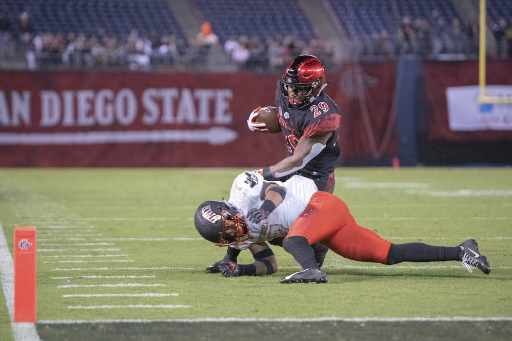 SAN DIEGO, CA - NOVEMBER 10: San Diego State Aztecs running back Juwan Washington (29) fights off a tackle during a NCAA football game between the UNLV Rebels and the San Diego State Aztecs on Nov ...