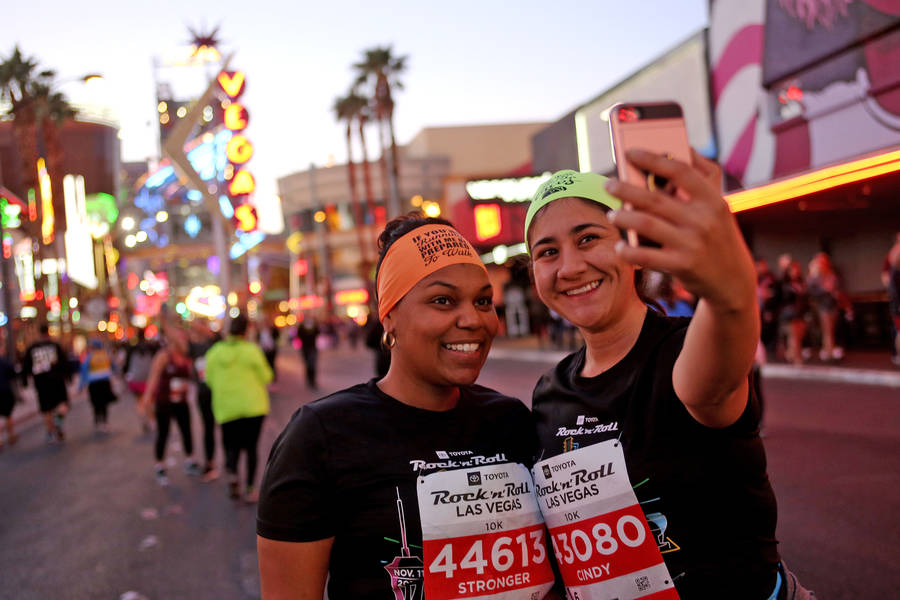 Jessica Fred, left, from Los Angeles, takes a selfie with Cindy Loza, from Long Beach, during the 10k race on Fremont Street for the Rock 'n' Roll Marathon in Las Vegas, Sunday, Nov. 11, 2018. Rac ...