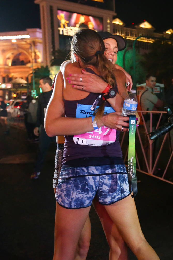 First place women's finisher Hannah McInturff hugs second place women's finisher Jessica Sams after she crosses the finish line during the 2018 Rock 'n' Roll Marathon on the Strip in Las Vegas, Su ...