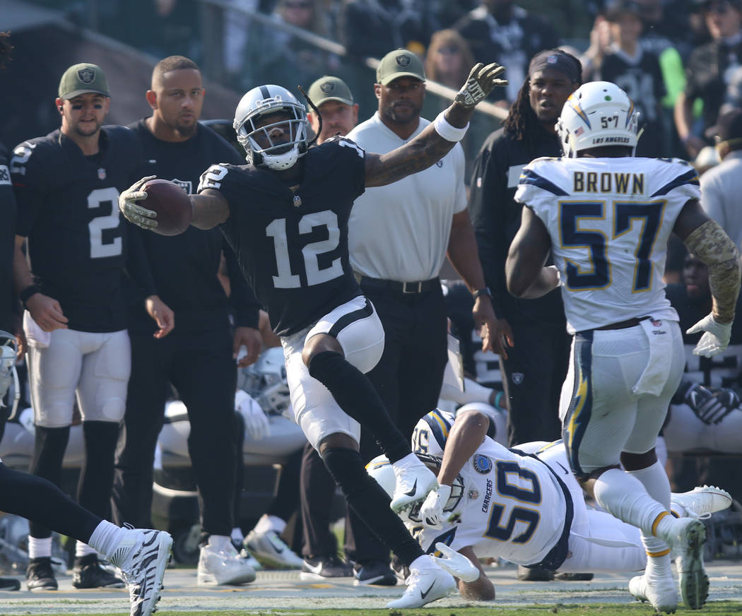 Oakland Raiders wide receiver Martavis Bryant (12) tries to stay in bounds as Los Angeles Chargers linebacker Hayes Pullard (50) tackles him during the first half of their NFL game in Oakland, Cal ...