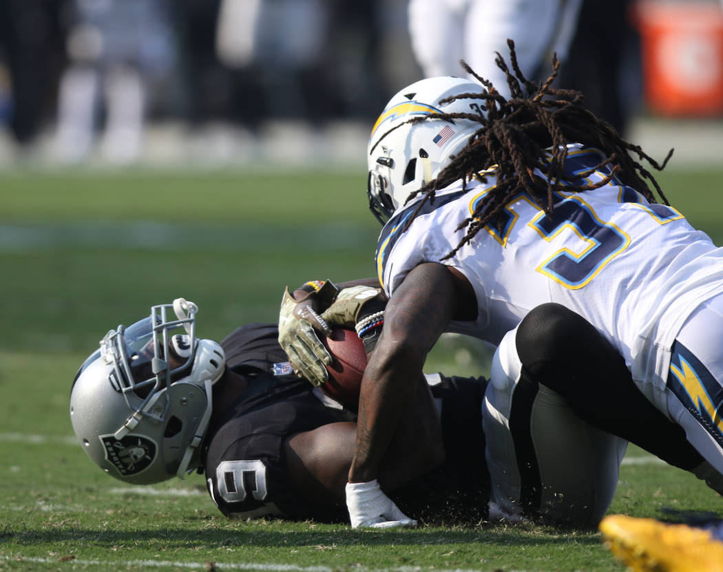 Oakland Raiders wide receiver Brandon LaFell (19) is tackled by Los Angeles Chargers strong safety Jahleel Addae (37) during the first half of their NFL game in Oakland, Calif., Sunday, Nov. 11, 2 ...