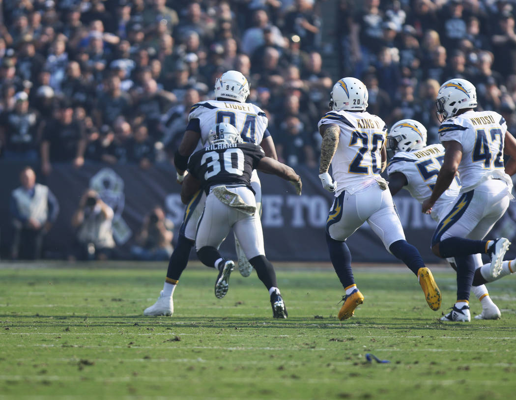 Oakland Raiders running back Jalen Richard (30) tries to chase down Los Angeles Chargers defensive tackle Corey Liuget (94) after forcing a fumble during the first half of their NFL game in Oaklan ...